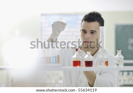 young man scientist in chemistry bright lab - stock photo