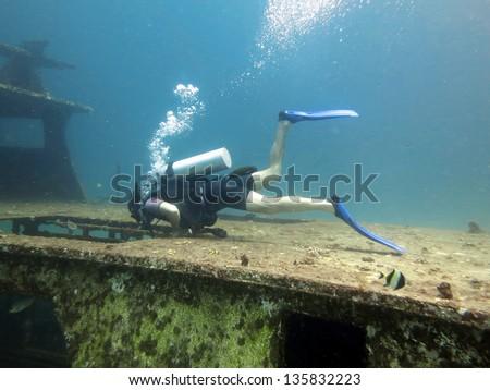 Young Man Scuba Diver between Water Surface near a shipwreck