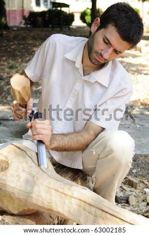 young man sculpting wood material - stock photo