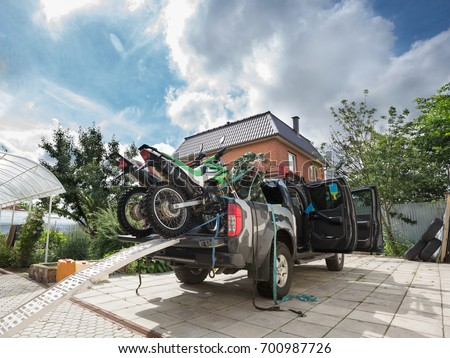 Young man securing two sports dirt bikes to the bed of the pickup truck using blue safety belt or tie-down straps, in the residential setting. #700987726