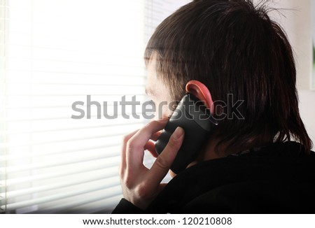young man see through the jalousie and talking on mobile phone