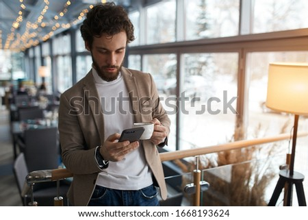 young man sending message to colleague. confident attractive young man holding smart phone and looking at it while standing in front of the big window in cafe, close up photo, free time, spare time Foto d'archivio ©