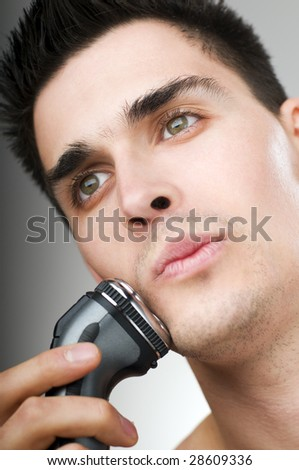young man shaving his beard off with an electric razor