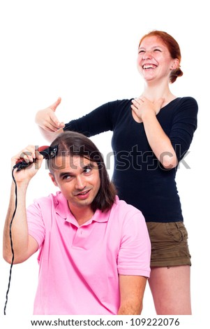Young man shaving his head with hair trimmer and woman laughing at him, isolated on white background. - stock photo