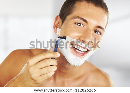 young man shaving in the bath. He is passing the razor for the beard while it looks at the mirror