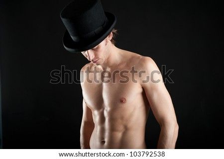 Young man shirtless with cylinder against black background.