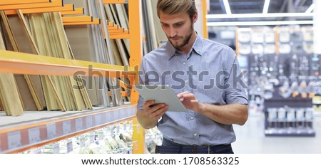 Young man shopping or working in a hardware warehouse standing checking supplies on his tablet. Foto stock ©