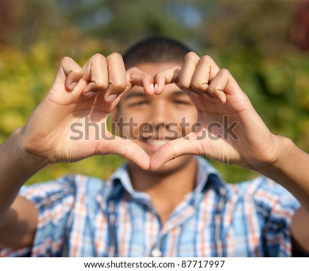 Young man show love sign outdoor