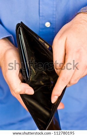 Young man showing his empty wallet