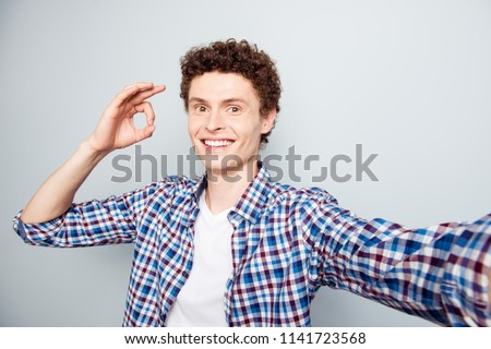 Young man showing ok sign shooting a selfie photo on camera of his smartphone isolated on light gray background