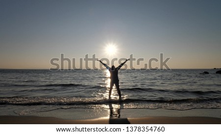 Young man silhouette running to the sea and lift up hands, slow motion #1378354760