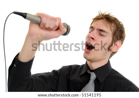 Young man sings into a karaoke microphone isolated on white