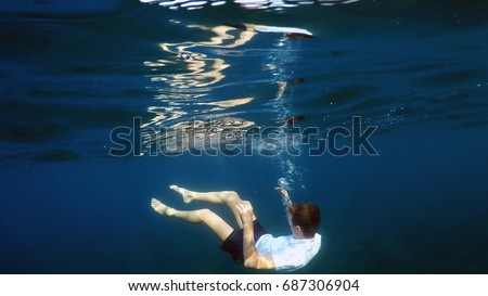 young man sinking into the sea #687306904