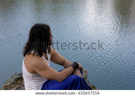 Young man sits on  lake and watches nature. Relax. #633657254