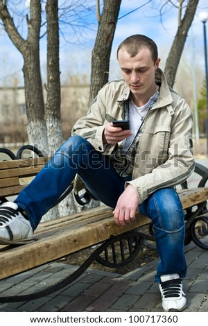 young man sits on small bench