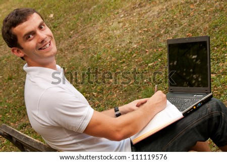 Young man sits on the bench with his laptop