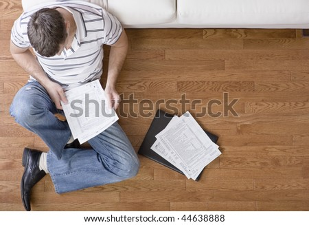Young man sits on the floor as he looks through paperwork. Horizontal shot.