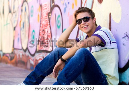 Young man sitting against graffiti wall - stock photo