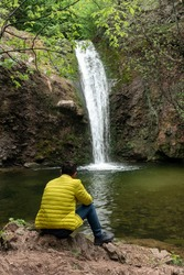 Young man sitting alone near waterfall watching falling stream of water. Getaways on wild nature, adventure vacations outdoor, hiking, mind refreshing, local eco travel. Rhodope Mountains, Bulgaria