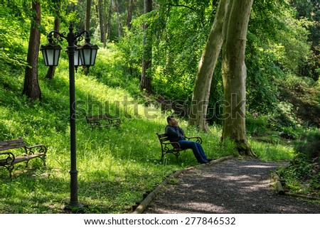 Young man sitting alone on a bench in a park. Concept for grief or sadness