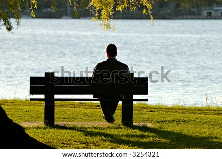 Young man sitting alone on park bench, under a willow tree, looking down to the water in late afternoon