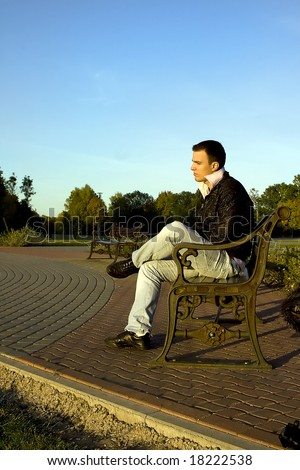 Young man sitting alone on the bench
