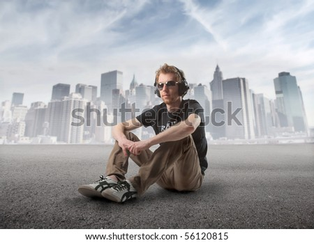 Young man sitting and listening to music with cityscape on the background