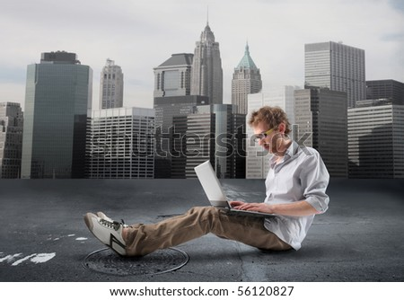 Young man sitting and using a laptop with cityscape on the background