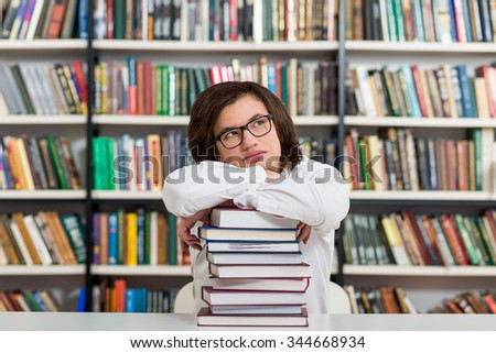 young man sitting at a desk in the library with his arms on a big pile of books and chin on them, head half turned to the top,  thinking,  a concept of knowledge, blurred books at the back