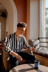 Young man sitting at a table in a cafe. Guy with a phone in a cafe on a chair. Stylish guy spends time with phone and coffee. Trip.