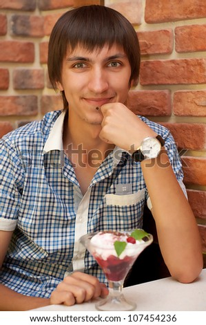 Young man sitting at cafe with cherry ice cream