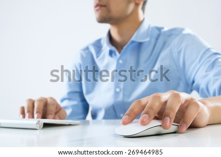 Photo of  Young man sitting at desk and working on computer