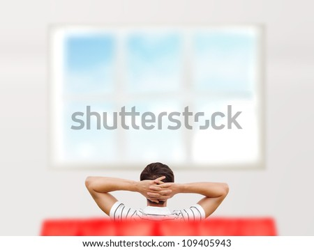 Young man sitting at his new home and looking at window. Photo from behind