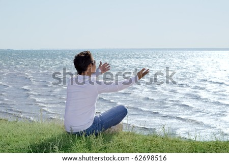 young man  sitting at precipice and looking on the sea shore