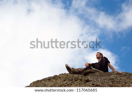 Young man sitting  at the edge of rock and enjoying seaside view, against blue sky with clouds
