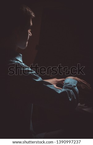 young man sitting at the piano. boy emotionally plays the keyboard instrument in the music school. student learns to play. hands pianist. black dark background. vertical. #1390997237