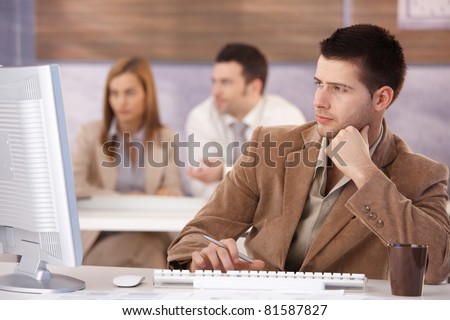 Young man sitting at training course, using computer.?