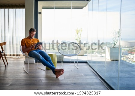 Young man sitting back in a chair in his living room at home browsing online with a digital tablet