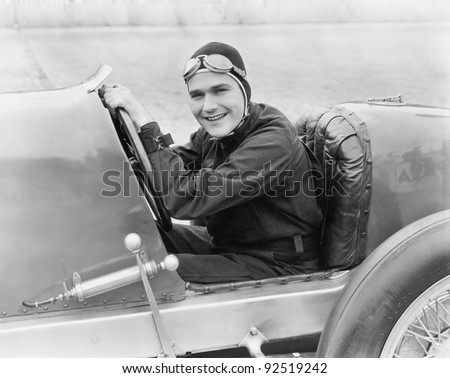 Young man sitting in a race car with a big smile