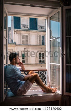 young man sitting in a window looking out over the city Paris. Men enjoy sun in window of hotel room #1177120402