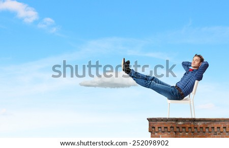 Young man sitting in chair with legs up and relaxing #252098902