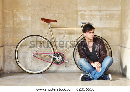 Young man sitting in front of his fixed-gear bicycle, also called fixie