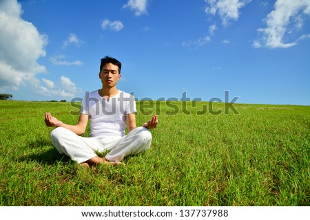 Young man sitting in lotus position out side