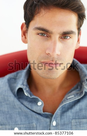 Young man sitting in red chair