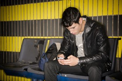 Young man sitting in station typing on smartphone waiting for subway train