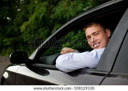 Young man sitting in the car smiling