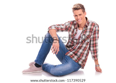 young man sitting/laying on the floor and smiling to the camera, on white background