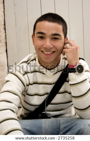 Young man sitting, looking at the camera with a big smile on his face. Attention inspectors: I have removed all the identifying markings from the watch face.