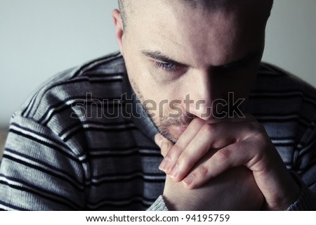 Young man sitting looking upset