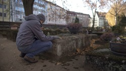 Young man sitting near grave on ancient cemetery praying, mourning for relatives